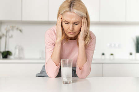 A middle-aged woman suffering from headache, holding head, massages the temples and feels hurt, effervescent pain reliever tablet dissolves in glass of water. Disease treatment concept