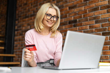 Glad mid age woman using a laptop for e-bancing, inputs credit card number to make online transaction, a smiling blonde lady is shopping online, transferring money, receve paymant