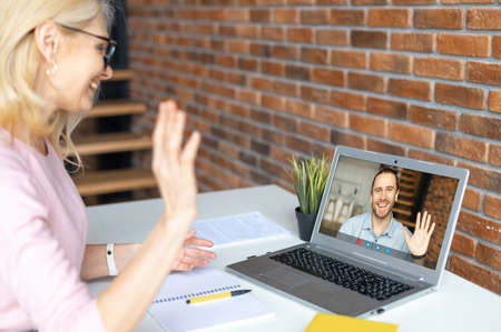 A friendly middle-aged female office worker wearing glasses, sitting at the desk in the office, waving at the laptop, greeting participants of online conference, saying hello to male student, coworker