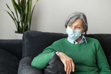 Thoughtful senior gray-haired lady wearing green sweater and a protective face mask, placed her hand on a couch and looking away, waiting in the queue for her turn to attend a medical appointment