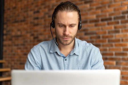 Portrait of a focused millennial young businessman in a headset looking on the laptop, hipster customer service representative sitting against the brick wall, concentrating on the customer problem