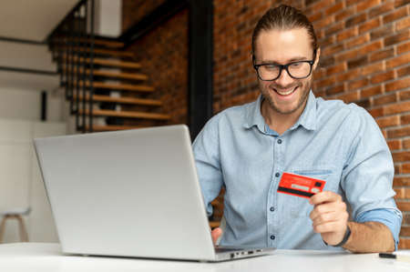 Young bearded businessman wearing glasses using laptop and credit card for online payment at home, disabled guy in wheelchair holding the debit card for internet banking account, ordering food