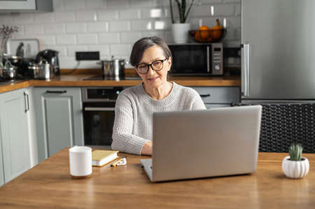 A mature business woman wearing stylish eyeglasses is using laptop for remote work from home, a senior lady answering emails, preparing report, researching