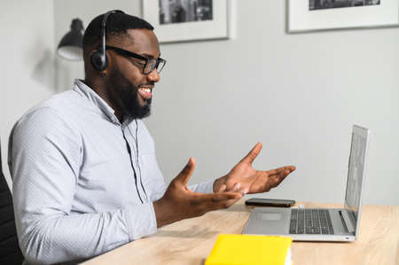 Young intelligent African-American teacher sitting at the desk and having coaching session online with students from business school, working on a laptop, using headphones with a microphone