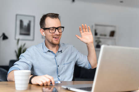 A smiling young man waving hello into webcam, a guy has video call on the laptop sitting at the desk in a home office. Video conference, online meeting Imagens