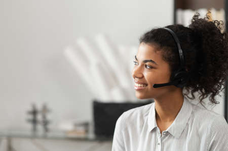 Young thoughtful African American female sudent in a headset is listening to an online webinar, studing remotely from home or working in the customer service department as a call center operator Stock Photo