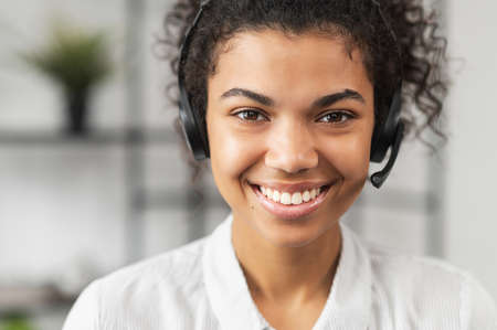 Headshot of friendly African American millennial woman in headset, smiling and working in emergency helpline or in the customer service department as call center operator, helping client with inquiry