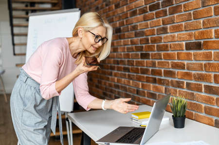 Modern and skilled middle-aged business woman looks at the laptop screen and recording a voicemail on the smartphone, female project manager makes a remark and sends to an executor Фото со стока