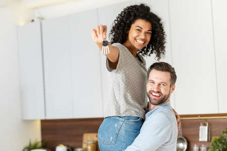 Dreams came true. Excited multiracial couple buying a property, got a mortgage apartment. A guy is carrying his beautiful girlfriend on the arms with keys in the hand