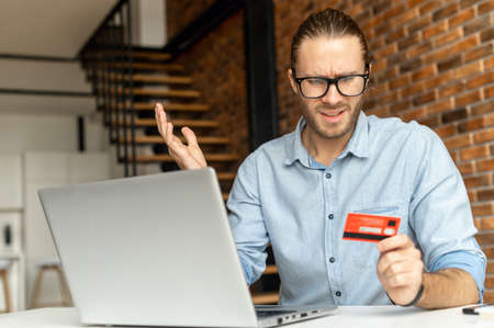 A puzzled guy sits at the desk with a laptop, holds credit card in hand and looks at it with incomprehension, a man could not complete the transaction online, not enough money on the card