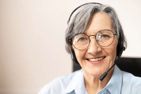 Close-up of the face of a charming beaming elegant elderly lady, wearing headset, glasses, smiling and looking at the camera. Portrait of a senior customer service representative sitting in the office Imagens