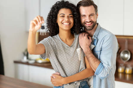 Cheerful young multi ethnic couple in love stand in embraces the kitchen, holding keys of a new house. Joyful international newlywed moved in new apartment, got a mortgage, moving day