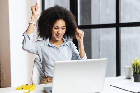 Excited lucky mixed-race businesswoman raised fists up celebrating success, making yes gesture, looking at laptop, passed the test with a high score, got promoted, won lottery or gift, victory concept