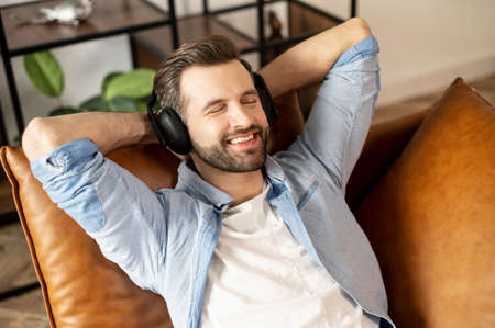 Handsome smiling guy wearing headphones enjoys music, attractive bearded man rests with a favorite tracks, lying on the comfortable sofa with eyes closed and hands behind head, daydreaming, resting Standard-Bild