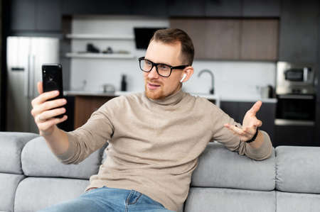 A young handsome man wearing eyeglasses using a smartphone for video chat, video call sitting on the couch at home. A smiling guy is talking online via video connection on the cellphone