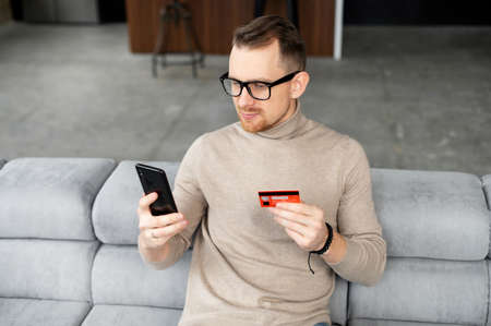 Cheerful young man makes purchase online. A guy wearing casual shirt holds a mobile phone and a credit card, orders food. Smiling guy is using smartphone and debit bank card for paying in e-shop Standard-Bild