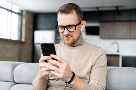 Handsome guy is using smartphone for messaging, texting, a young man in smart casual wear sitting with a phone in the hands, typing a message, chatting in the networks