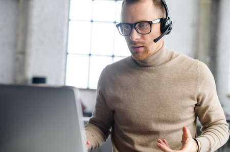 A friendly guy with a headset using laptop for communication with employees, coworkers, video conference. A support officer is talking with a customers, helpline