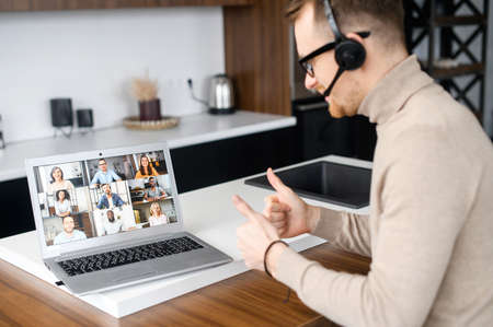 Back view on the laptop screen with a many diverse people on it, a guy with a headset using computer app for communication with employees, coworkers, video conference concept