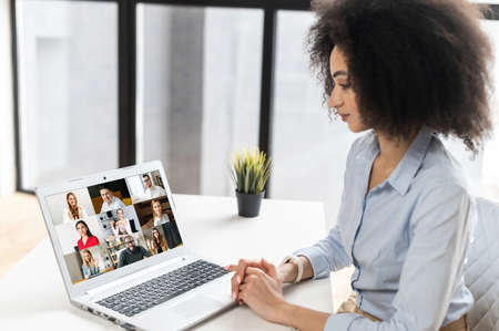 Multiracial woman sitting at the laptop, chatting with friends or colleagues via video meeting,discussing the new project, teaching online,making video call to group of diversw people