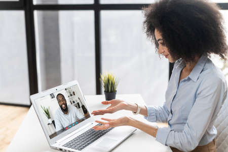 Young woman with curly hairstyle sitting at the laptop, chatting with friends,colleague,talking about the news,work,new project,working from office,smiling,teaching online,attending an online meeting