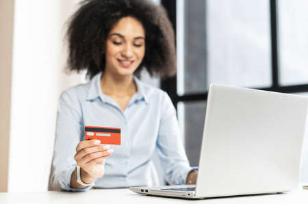 Successful multiracial businesswoman with curly hairstyle,smiling,sitting at the laptop,paying in the Internet,buying online,working from office,smiling,holding a credit card, buying online courses Standard-Bild