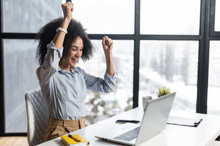 African-American woman with curly hairstyle hands up,at the desk with open laptop,wide smile,excited by the news,celebrating her success,accepted for internship,admitted to university, got a letter Standard-Bild