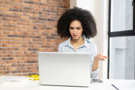 Young multiracial businesswoman with curly hairstyle sitting at the laptop, at office,discussing,taking part on a work meeting, talking to her employee or partner,looking at laptop screen,saw an error