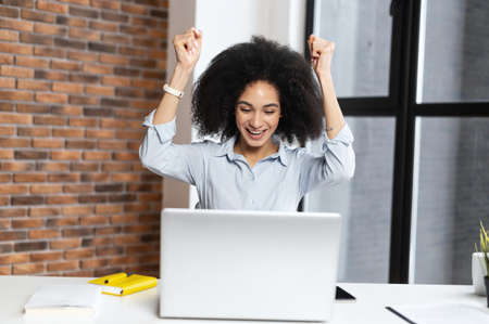 Happy young multiracial student hands up,in front of the computer,with wide smile,celebrating her success,got a scholarship,admitted to university,received a long-awaited letter,ended project