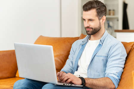 Handsome focused guy wearing casual shirt using a laptop sitting at home on the couch, web browsing, working remotely from home. A young man is typing on the keyboard sitting on the sofa