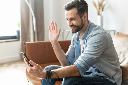 A young handsome guy using a smartphone for video call, smiling man in casual wear is waving hello into webcam, has virtual meeting with friends or employees sitting on the couch at home