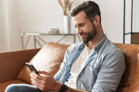 Smiling guy wearing casual outfit messaging, texting on the smartphone. Side view a young man sits on the modern sofa and using mobile app, scrolling feed news, websurfing, playing game