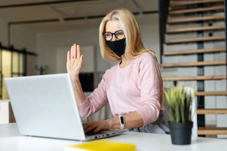 Elegant middle-aged woman sitting at the laptop in the office during a pandemic,greetings colleagues,chatting with friends,smiling, gives the high-five,looking at laptop screen,on an online meeting
