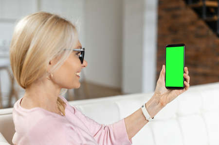 Beautiful positive middle-aged woman smiling and chatting on the smartphone, talking with family or friend,watching the news,working at home. Empty phone screen, mock-up