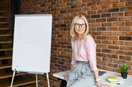 Successful businesswoman with glasses stands in front of an interactive whiteboard and presenting a new strategy for the company,using drawn graphics,showing how much income they can get