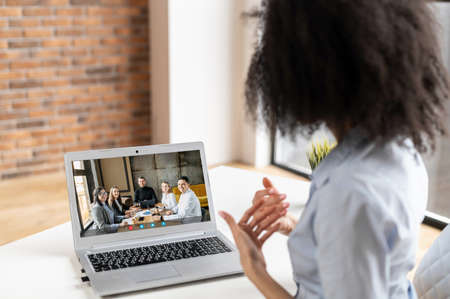 Intelligent young mixed-race businesswoman sitting at the desk and presenting a project to a group of clients or colleagues via laptop, having a virtual online meeting during coronavirus outbreak