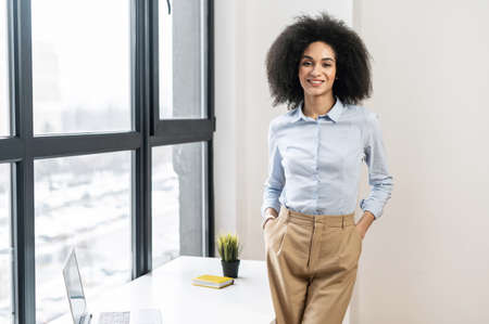 Successful relaxed young mixed-race female entrepreneur or a businesswoman with Afro hairstyle in casual clothes standing with hands in pockets in the office with the panoramic view, looking at camera Standard-Bild