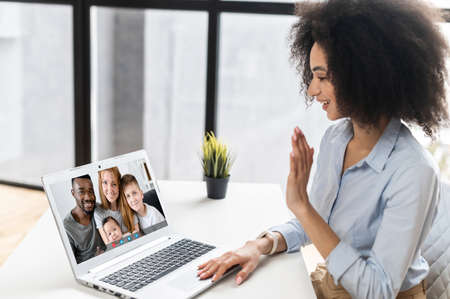 Young mixed-race African American businesswoman sitting at the desk in the office and video-calling chatting with family, using laptop and social media application to stay connected during covid-19 Standard-Bild