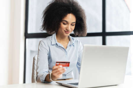 Young mixed-race businesswoman sitting at the desk in front of laptop, holding credit card, entering the gift card number, feeling excited to purchase items from an online store, order food, pay bills Standard-Bild