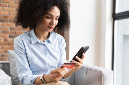 Close-up of an African American mixed-race businesswoman with curly hair holding mobile phone, entering credit card number to make an online transaction, paying bills, doing online shopping from home