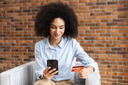 Attractive African American mixed-race businesswoman with curly hair holding mobile phone, entering credit card number to make an online transaction, ordering food, doing online shopping from home