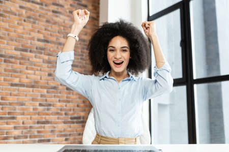 Happy young businesswoman with short curly hair hands up, sitting in front of the computer,with wide smile,rejoices her success,got a new job,received a salary,finished a project,in the office,winner