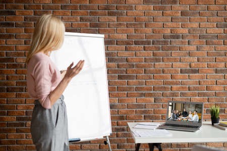 Successful businesswoman showing on interactive whiteboard options for increasing sales,presenting a new strategy for the company,using drawn sale graphics,on online meeting with team,distance work