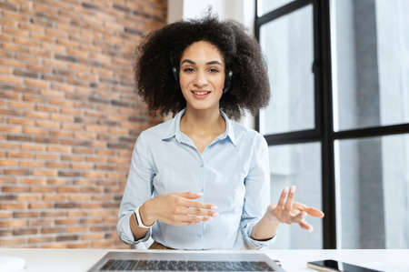 Young multiracial woman sitting at the laptop,chatting with headset,gestures with his hands, explaning,consulting online,on a meeting,talking in front of keyboard,smiling,looks into the camera Standard-Bild