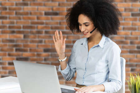 Young woman with nice short hairstyle sitting at the laptop with one hand up, greeting,consulting online,leading a conference,talking at the laptop,working in the office,smiling,calling her boss