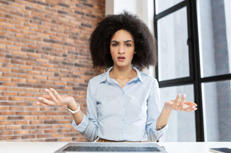 Young multiracial woman with curly hairstyle sitting at the laptop,does not understand what happened,at office, discussing,arguing,looking at laptop screen,wants to convince that she is right Standard-Bild