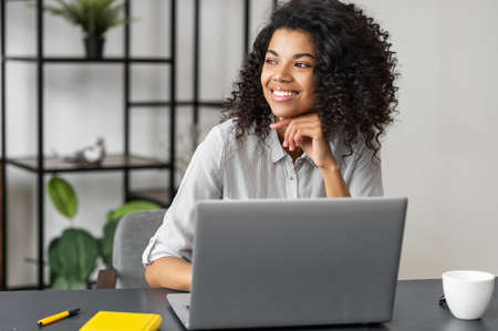 Pretty smiling young African American woman with Afro hairstyle sitting at the desk and looking in the window, taking a break from working on a laptop, dreaming about weekend plans or a vacation Standard-Bild
