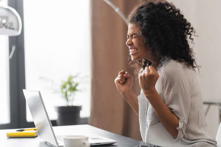 Happy excited African American businesswoman celebrating success, winner of the competition raising hands up, expressing joy from achieving goals, sitting at the desk with an open laptop in the office