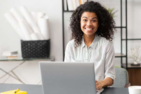 Excited young African American female office worker businesswoman with Afro hairstyle sitting at the desk with laptop, looking at the camera. Portrait of a working mixed-race woman with positive vibe