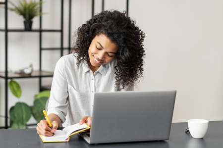 Positive African American woman student sitting at the desk at home in the modern office, using the laptop for distance video communication, studying, working, meeting online, and making notes Standard-Bild